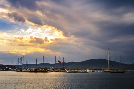 boats and yachts docked near embankment in port of Bulgarian town Sozopol in evening light Stock Photo