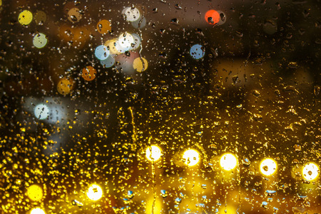 abstract background raindrops on glass on background of blurred warm  with cool blue and purple lights with bokeh effect