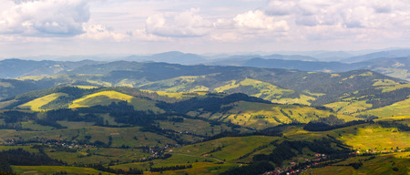 clearing: summer landscape. village on the hillside. forest on the mountain light fall on clearing on mountains Stock Photo