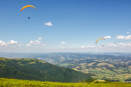 Three persones skydiving  flying over the mountains. parachute extreme sport Stock Photo