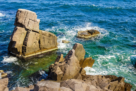 sea wave attacks the boulders of rocky shore and is broken about them Stock Photo