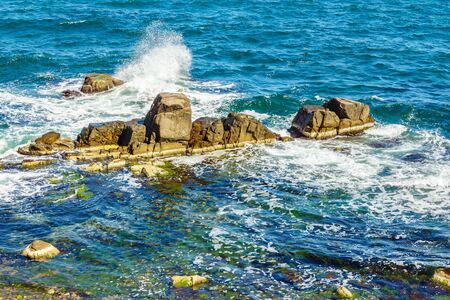 sea waves attacks the boulders of rocky shore and is broken about them