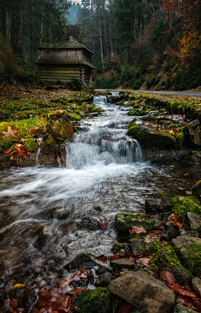 mountain river with stones and moss in the forest near the abandoned wooden house near the hillside Stock Photo