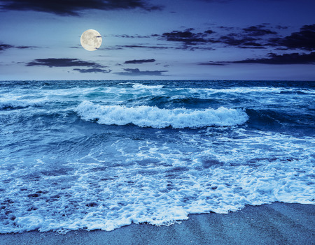 green and mighty sea wave attacks the sandy beach and break on them at night in full moon light