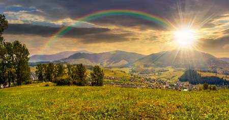 summer rural landscape. meadow with few trees near the village in mountain valley in evening light under the rainbow Stock Photo