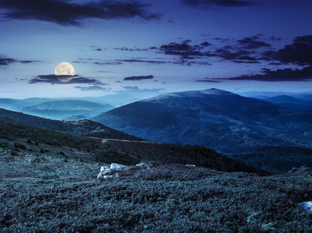white sharp boulders on the grassy meadow on the edge of hillside in  high mountain range at night in full moon light Stock Photo