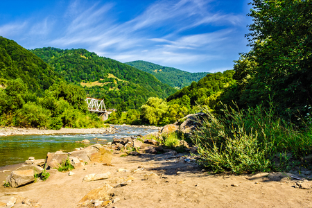 shore of a mountain river with stones and iron bridge among the forest in fural area Stock Photo