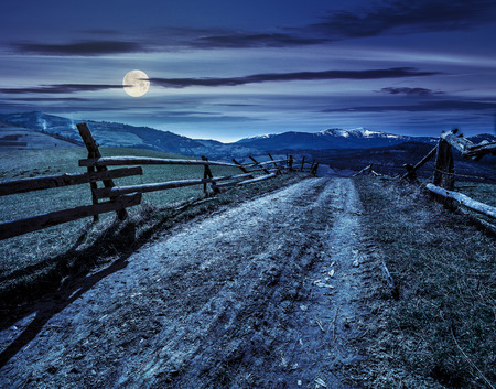 fence near the road through the  rural meadow in mountain region in spring time at night in full moon light
