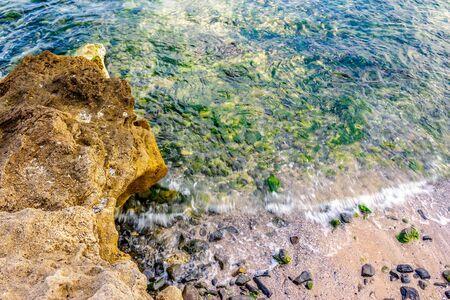 wave rolls onto the rocks on the sandy sea coast Stock Photo