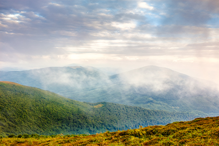 cold morning fog on hot sunrise in the mountains