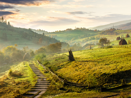 stone steps down the hill in to village in foggy mountains at sunrise