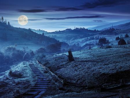 石段と丘を下って霧山の村に夜満月の光の中 写真素材