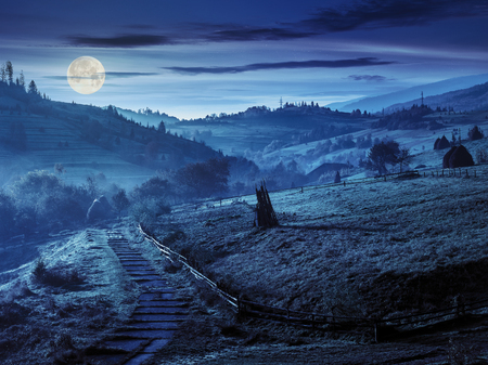 stone steps down the hill in to village in foggy mountains at night in full moon light