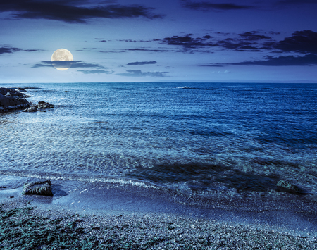 boulders, stones and seaweed on the sandy coast of the sea at night in full moon light