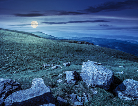 white sharp boulders on the hillside meadow with green grass in high Crapathian mountains at night in full moon light