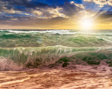 close up of huge, green and mighty sea wave craches on sandy beach and break in evening light Stock Photo