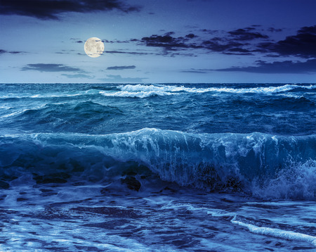 close up of huge, green and mighty sea wave craches on sandy beach and break at night in full moon light Stock Photo