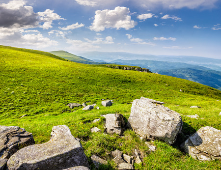 white sharp boulders on the hillside meadow with green grass in high Crapathian mountains