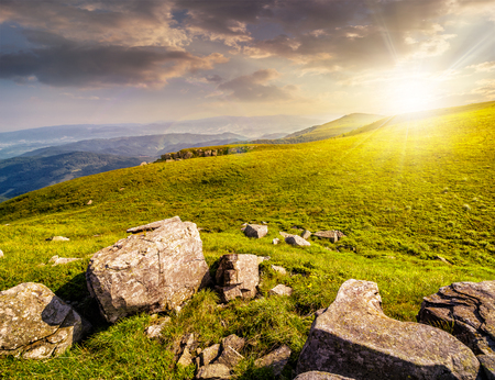 white sharp boulders on the hillside meadow with green grass in high Crapathian mountains in evening light