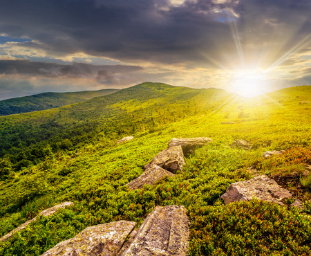 white sharp stones and boulders among green grassy meadow on the hillside on top of  mountain range in evening light