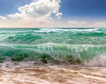 close up of huge, green and mighty sea wave craches on sandy beach and break Stock Photo
