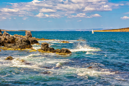 Small boat sails at distance in the sea. waves break on the huge boulders  on the rocky shore. on the other side of of seascape can be seen bald island Stock Photo