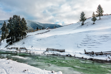 frozen river near the hillside with spruce trees in Carpathian rural area