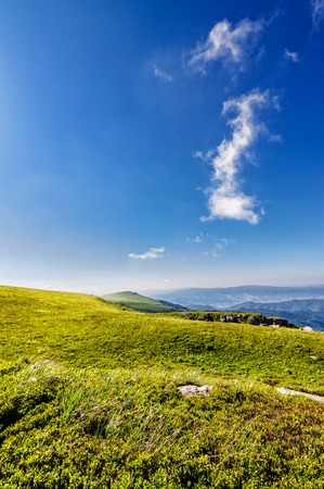 green grass on  hillside meadow in high mountains under the cloudy blue sky Stock Photo
