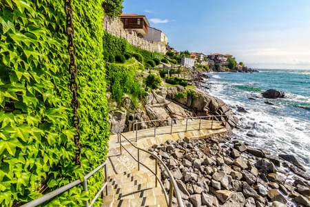 Ancient european city Sozopol on a rocky shore near sea in summer. piere and steps to sea shore