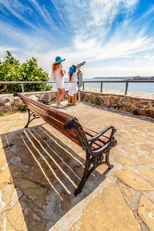 Mother and daughter standing on a seaside observation deck with a bench and looking into bincular