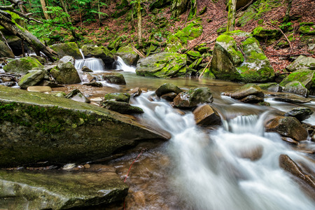 small cascades on the forest river among huge bouders covered with moss. taken with long exposure Stock Photo