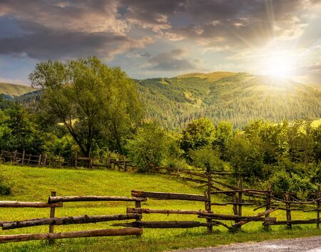 hillside: composite image of wooden fence on agricultural grassy meadow with trees on hillside in high mountains in evening light Stock Photo