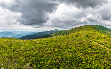 summer mountain landscape under the sky with heavy clouds