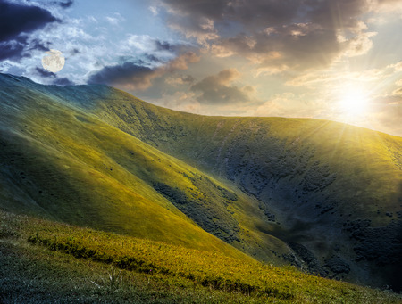 hillside: day and night composite image of green grass on hillside meadow in high mountains under the cloudy sky Stock Photo