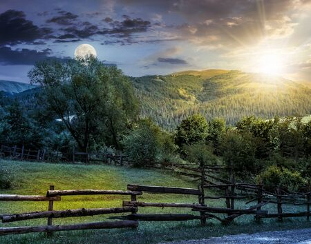 day and night composite image of wooden fence on agricultural grassy meadow with trees on hillside in high mountains at sunset