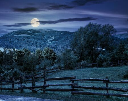 composite image of wooden fence on agricultural grassy meadow with trees on hillside in high mountains at night in full moon light