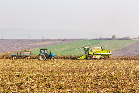 Mukachevo, Ukraine - November 6 2015: tractor and harvester in the field among the corn stalks in late fall  haze day