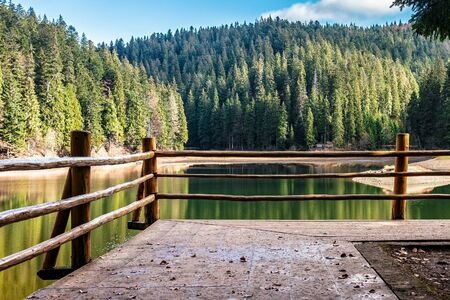 fence of wodden piere on the lake among spruce forest in mountains