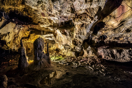 cave with colourful textured walls and stalactites and stalagmite lit from behind Stock Photo
