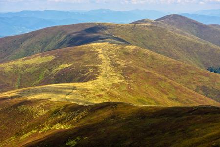 winding road through meadows of Borzhava mountain range in Carpathians late summer