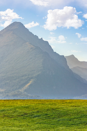 high rocky peak of Tatra mountains in evening haze behind the green field