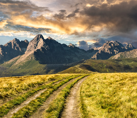 Composite Landscape image. Path through the meadow on hillside in Tatra mountains at sunset Stock Photo