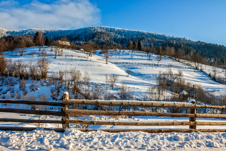 woodshed behind the fence on the hillside cowered with snow near conifer forest in winter mountains early in the morning Stock Photo