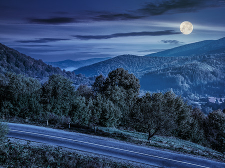 few trees on a hill side meadow near the mountain asphalt road at night in full moon light Stock Photo