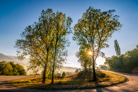 empty winding mountain road on a hillside in the early morning Stock Photo