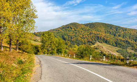 hillside: road through the hillside near autumn forest Stock Photo