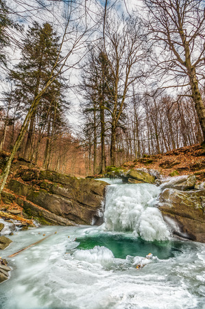 frozen waterfall over the huge boulder on the river among empty forest with old brown foliage on the ground Stock Photo