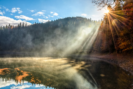 view on crystal clear lake with rocky shore and smoke on the water near the pine forest in fog at the foot of the mountain at sunrise Stock Photo