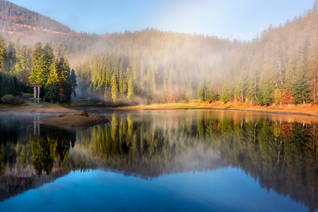 view on crystal clear lake with smoke and reflection on the water near the spruce forest in fog at the foot of the mountain at sunrise