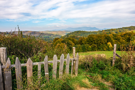 agricultural area: wooden fence on the hillside with forest in agricultural area in mountains early in the morning Stock Photo